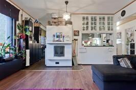 Olohuoneessa on varaava takka ja näkymä keittiöön