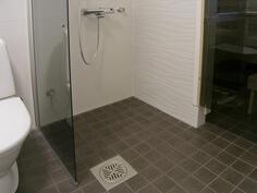 suihkutila erotettu kääntyvällä suihkuseinällä. Tehosteseinällä kuviolaatta.