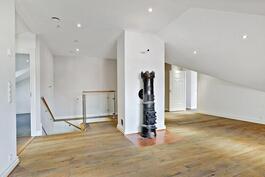 Antiikkinen valurautakamiina koristaa yläkerran aulaa/ En antik gjutgärnskamin i alrummet.