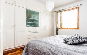 Makuuhuoneessa on seinän leveydeltä kaapistoja.