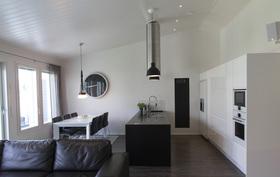 Integroitu keittiö, avoin ruokatila ja korkea katto luovat lisää tilan tuntua