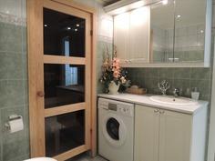 kylpyhuoneen kaapistot ja ovi saunaan