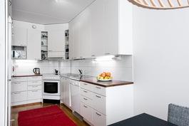 Toimiva keittiö, jossa on reilusti kaappi- ja laskutilaa.