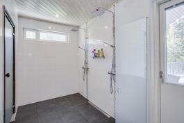 Tilavassa laatoitetussa pesuhuoneessa kaksi suihkua