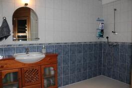 Saunaosaston tilava kylpyhuone, missä kaksi suihkua