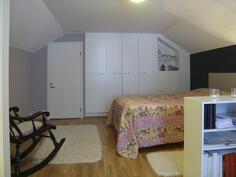 Yläkerran huone, taustalla naapuriin päin tilava vaatehuone ja komeroseinä