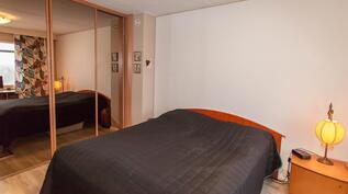 iso makuuhuone, jossa täyskorkea liukuovikaapisto