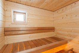 Saunan seinät leveää hirsipanelia ja lauteet lämpö