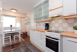Vaalean sävyinen keittiö on toimiva ja valoisa kokonaisuus..