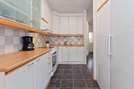 Vaalean sävyinen ja toimiva I-mallinen keittiö..
