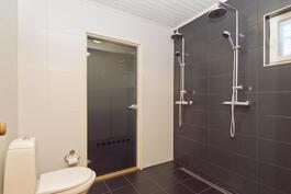 Tilava kylpyhuone kahdella suihkulla.