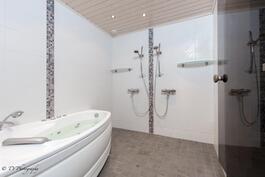 Moderni kylpyhuone porealtaalla ja kahdella suihkulla