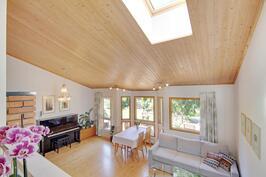 Kattoikkuna luo valoa olohuoneeseen, korostaen katon upeaa arkkitehtuuria.