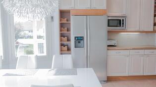 Keittiösä laadukkaat umpipuiset kalusteet, rosteriset kodinkoneet, jääpalakone pakastimen yhteydessä