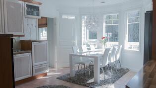 Valoisasta kauniista keittiöstä käynti kodinhoitohuoneeseen