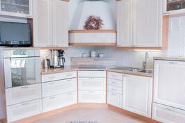 Keittiössä kauniit ja laadukkaat umpipuiset kalusteet, integroitu kulmaliesi