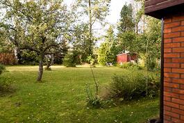 Iso puutrhamainen takapiha jossa on varasto sekä liiteri