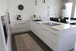 Täysin integroitu keittiö ja vaalea kivikomposiittitaso
