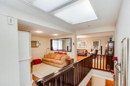 Näkymä portaikon yläpäästä takka-aulaan ja olohuoneeseen