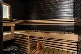 saunan kiukaassa riittää tehoja ja seinät ovat tunnelmallisen tummat