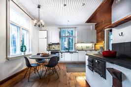 Nykyaikaistettu koneellinen keittiö, puuliesi, kuparikupu ja hirsiseinä.