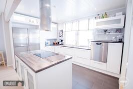 Keittiössä kauniit valkoiset kaapistot savulasiyksityiskohdilla ja led-valaistuksella