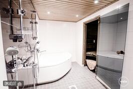 Kylpyhuoneessa kaksi suihkua, kulmakylpyamme, wc ja säädettävä led-valaistus