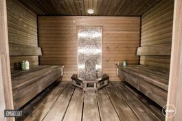 Komeassa saunassa korotettu laudelattia ja upotettu kiuas, led-valaistus kiukaan takana luo tunnelma
