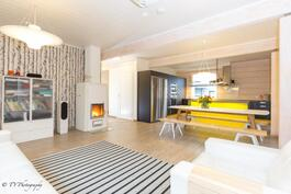 Avara olohuone- keittiö tila on jaettu keittiösaarekkeella, jossa ledi valot