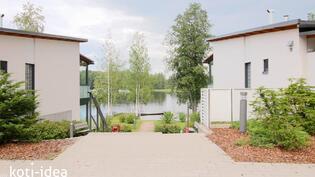 Talojen välissä häämöttää uimaranta ja laituri