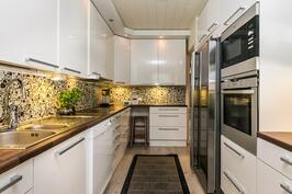 Keittiössä kauniit korkeakiiltoiset kaapistot ja rosteriset kodinkoneet.