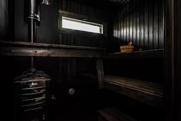 Tunnelmallinen tummaksi petsattu saunan puoli, jossa puukiuas..