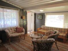 Kuvassa rantasaunamökin huonetila, jossa parkettilattiat ja kauniit maalatut paneeliseinäpinnat!