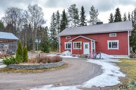 Viehättävä punainen talo ja pihamaa odottaa uusia asukkaitaan.