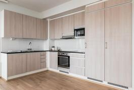 Keittiössä on laadukkaat kaapistot ja integroidut kodinkoneet.
