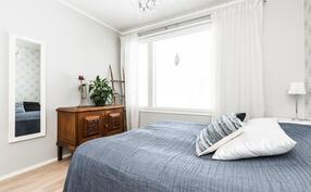 Makuuhuoneessa kauniit harmaaksi sävytetyt seinät tuovat lämpöä.