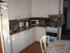 Keittiö olohuoneesta päin ja oikealla näkyy takkatilan oviaukko