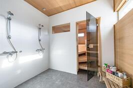 pesuhuoneessa on kaksi suihkua sekä ikkuna joka tuo tilaan luonnonvaloa