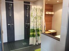 Kaksi suihkua, sauna oikealla ( varustettu aidolla puulämmitteisellä kiukaalla)