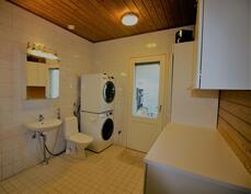 Kylpyhuoneen yhteydessä kodinhoitohuone ja käynti lasitetulle terassille
