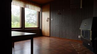Alakerran takkahuone, kaksi ikkunaa järvelle päin ja oven takana on pesutilat.
