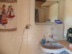 Wc:n seinissä on muovitapetti ja lattiassa muovimatto