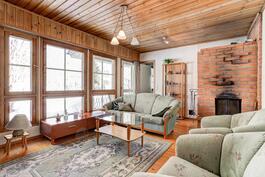 Olohuoneessa runsaasri ikkunapinta-alaa ja varaava takka.