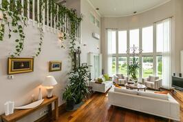 Olohuoneen isoista kahden kerroksen korkuisista ikkunoista jokinäkymä