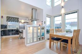 Upea vitriinikaapisto jakaa ruokailutilan ja keittiön kauniisti.