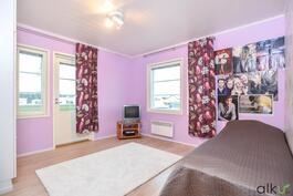 Yläkerran toisessa makuuhuoneessa loistavat tilat ja käynti parvekkeelle.