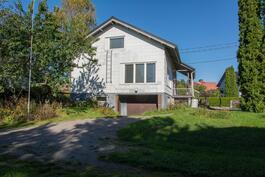 Talo katsottuna puutarhan suunnasta. Kellarikerroksen autotallin ovet näkyvät talon oik.alakulmassa.