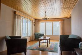 Olohuone on valoisa kokonaisuus, yhteys ruokahuoneeseen.