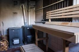 Sauna perinteisellä puulämmitteisellä kiukaalla ja padalla.