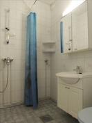 Kylpyhuoneessa laattalattia ja kaakeloidut seinät.